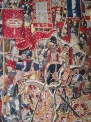 Le roi Alphonse V et son étendard à la devise de la roue de moulin lors de l'expédition contre Arzila en 1471. Tapisserie de Pastrana.